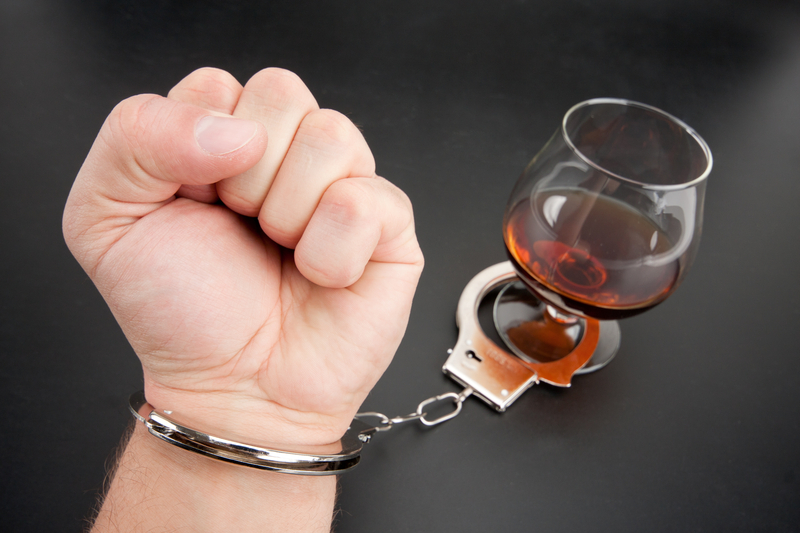 A hand locked to glass of alcohol